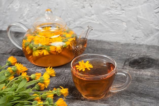 Tazza di tè alle erbe e teiera trasparente e fiori di calendula su fondo di legno. il tè alla calendula fa bene al tuo concetto di salute.