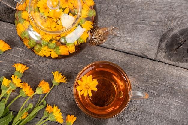 Tazza di tisana, teiera trasparente e fiori di calendula su fondo di legno.