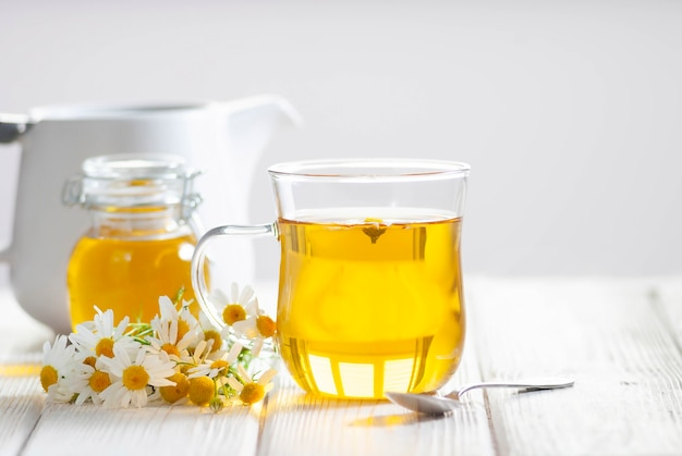Tazza di tisana con fiori di camomilla e miele su fondo di legno bianco