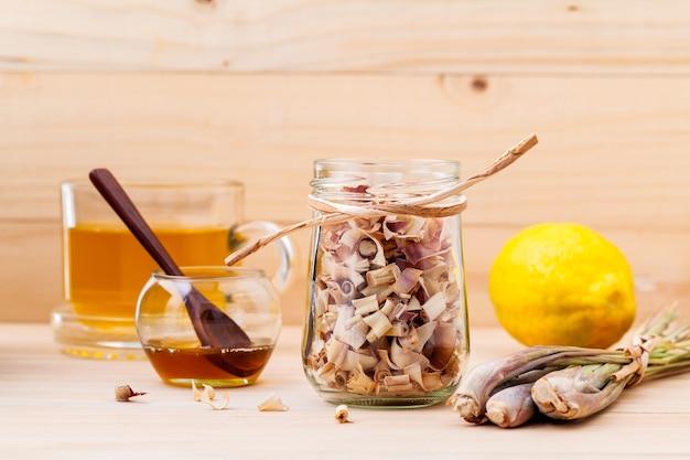 Tazza di tisana con citronella, miele e limone secchi su fondo di legno.