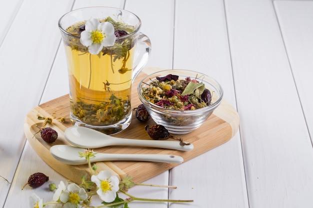 Tazza di tisana con cinorrodo, camomilla, erbe sul tavolo di legno bianco