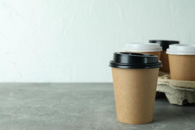 Portabicchieri con tazze da caffè sul tavolo grigio testurizzato