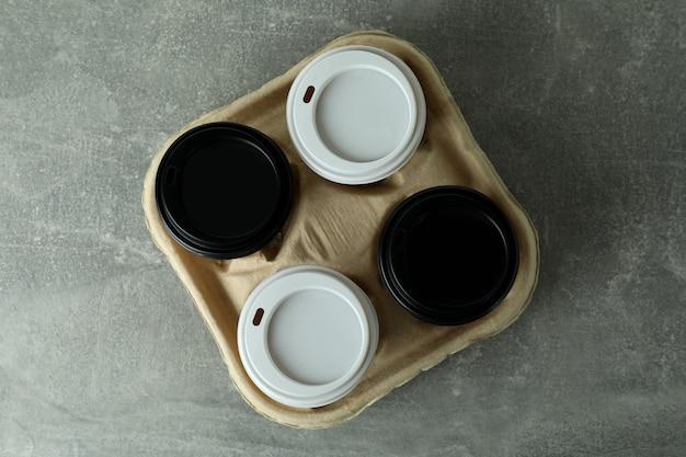 Portabicchieri con tazzine da caffè su grigio testurizzato