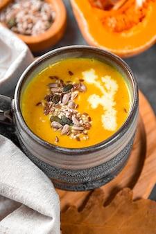 Tazza di zuppa di zucca fatta in casa con semi di semi di sesamo e semi di lino primo piano caldo cibo autunnale