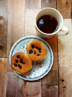 Una tazza di caffè nero caldo con muffin all'uvetta su uno sfondo di legno