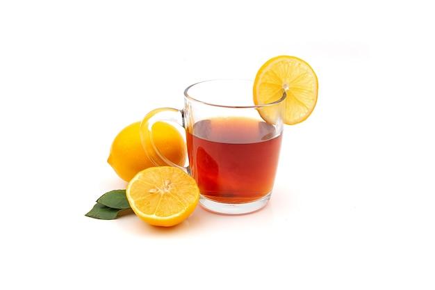 Una tazza di tè nero o verde caldo con limone e zenzero su uno sfondo bianco. ingredienti contro influenza e virus.