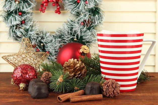 Tazza di cacao caldo con cioccolatini e decorazioni natalizie sul tavolo su fondo di legno