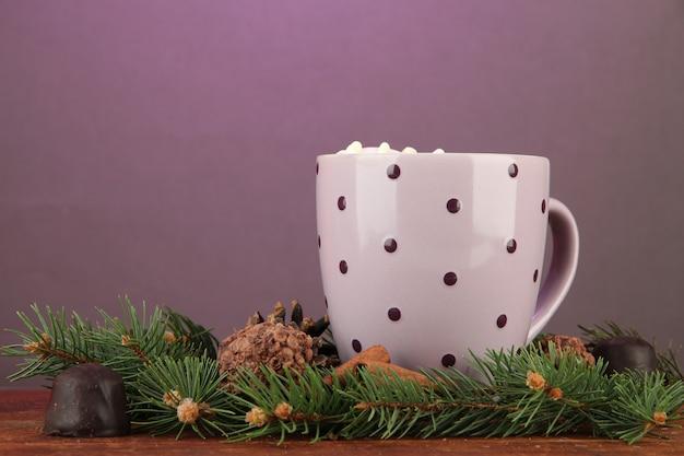 Tazza di cacao caldo con cioccolatini e rami di abete sul tavolo su sfondo scuro
