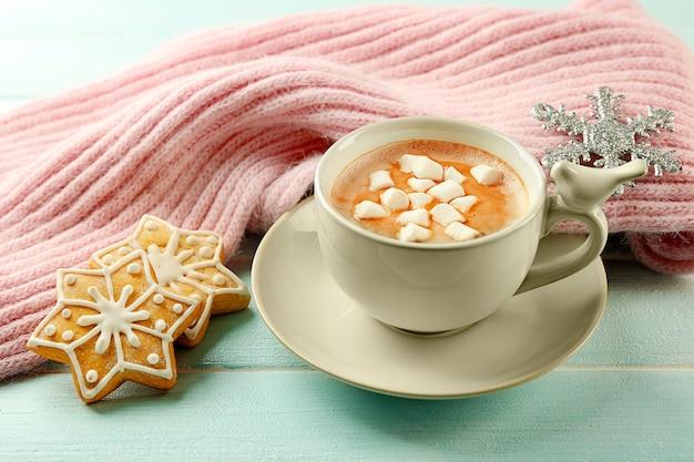 Tazza di cacao caldo con marshmallow, biscotti e sciarpa calda sul tavolo blu