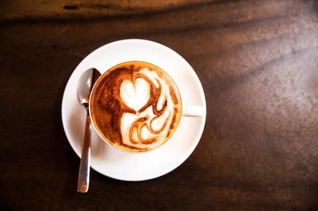 La tazza di cappuccino caldo è sulla tavola di legno. è un'arte sul latte.