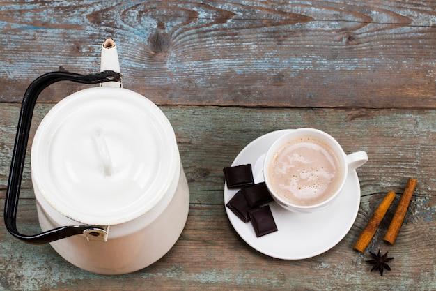 Tazza di cioccolata calda o cacao e bollitore vintage su sfondo di legno.