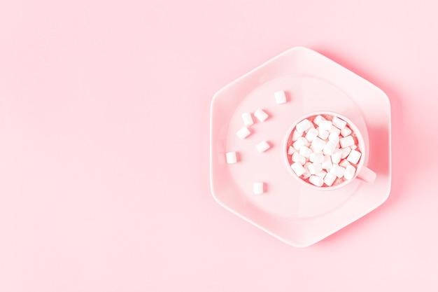 Tazza di cioccolata calda e marshmallow su uno sfondo rosa pastello.