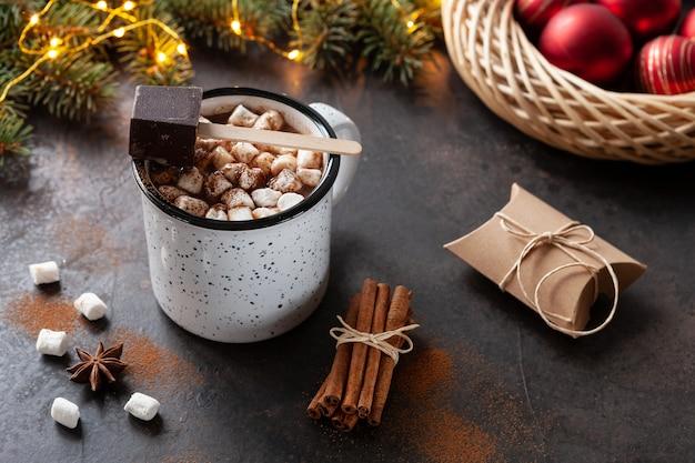 Una tazza di cioccolata calda con marshmallow, rami di abete, decorazioni natalizie