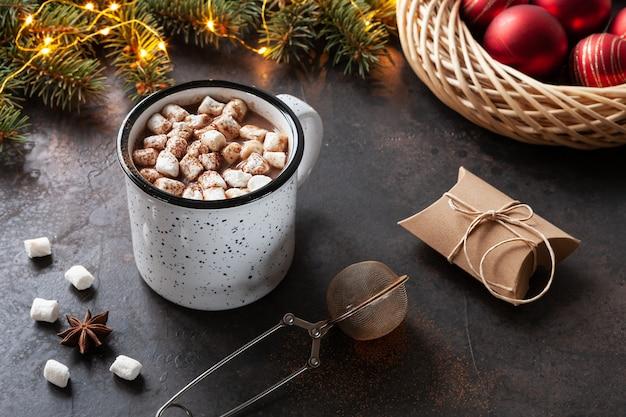 Una tazza di cioccolata calda con marshmallow, rami di abete