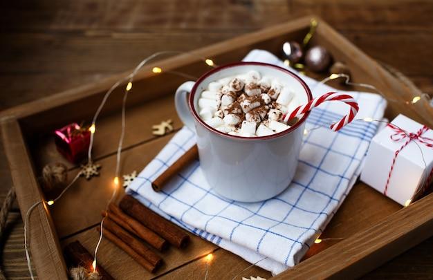 Una tazza di bevanda calda di natale su uno sfondo di legno intorno a un bastoncino di cannella e regali di natale. la vista dall'alto