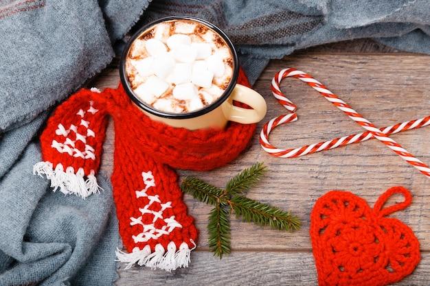 Tazza di cioccolata calda o cioccolato con sciarpa rossa, sciarpa fatta a mano e bastoncino di zucchero natalizio su tavola di legno, copia spazio. concetto di pianificazione di natale. disposizione piatta, vista dall'alto