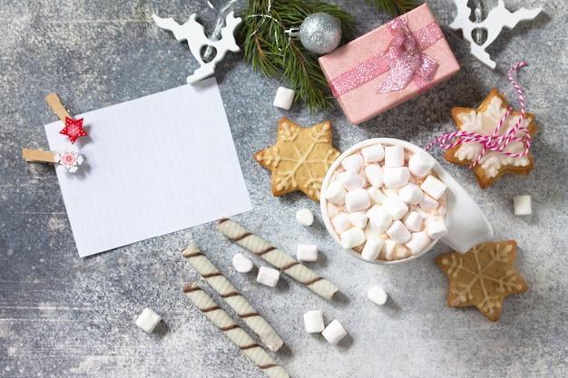 Una tazza di cioccolata calda con marshmallow e cottura natalizia su un piano di lavoro in pietra vista dall'alto