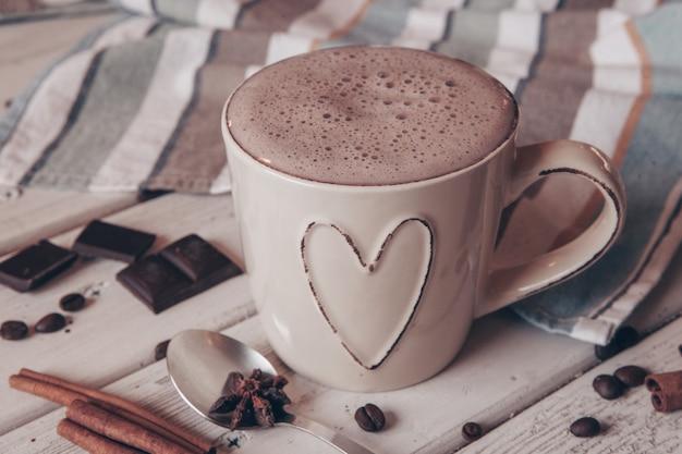 Tazza di cioccolata calda con marshmallow e bastoncini di cannella