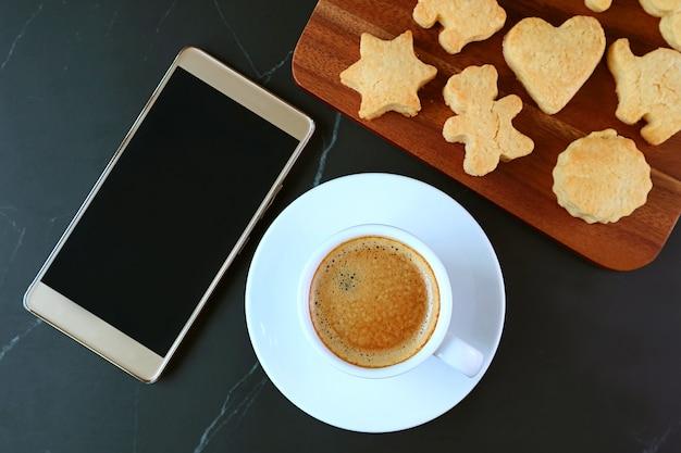 Tazza di caffè caldo e uno smartphone con schermo vuoto con adorabili biscotti a forma di animale
