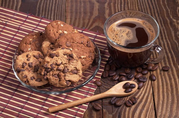 Tazza di caffè caldo e biscotti al cioccolato in piatto su legno scuro