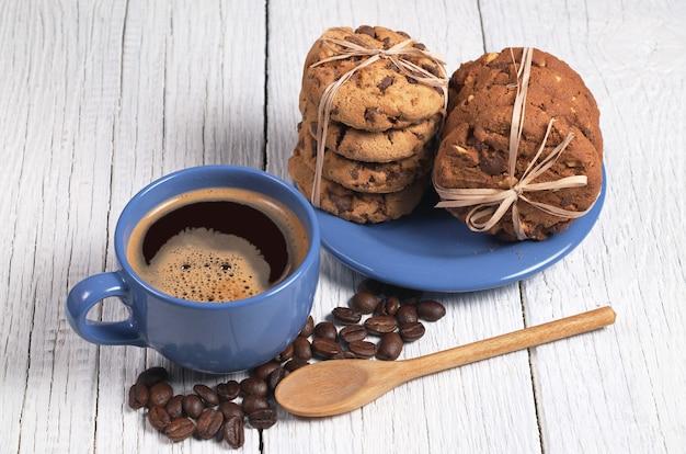 Tazza di caffè caldo e biscotti al cioccolato legati con un nastro nel piatto su un tavolo di legno bianco