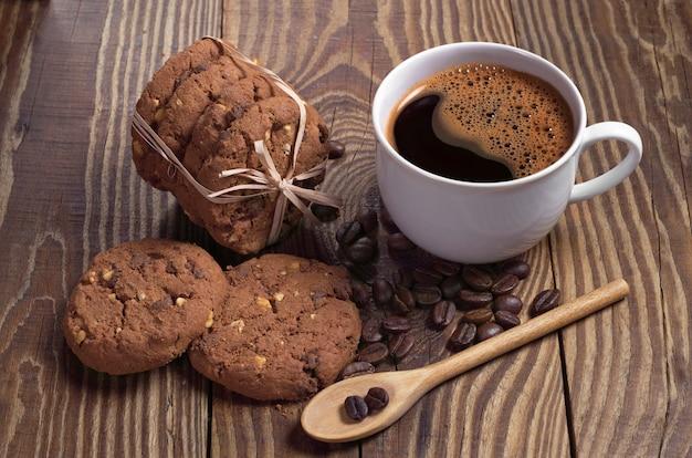 Tazza di caffè caldo e biscotti al cioccolato legati con nastro sul tavolo di legno