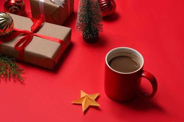 Tazza di caffè caldo e scatole regalo di natale su sfondo rosso.
