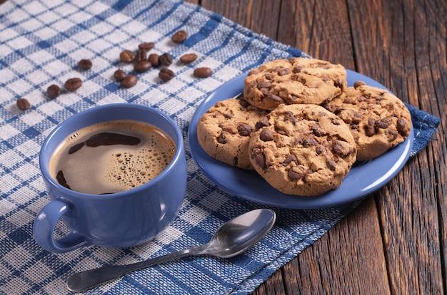 Tazza di caffè caldo e biscotti con cioccolato per colazione su tavola in legno rustico. stoviglie e tovaglie blu