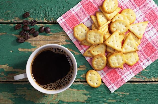 Tazza di caffè caldo e cracker con sapore di formaggio su un vecchio tavolo di legno verde, vista dall'alto