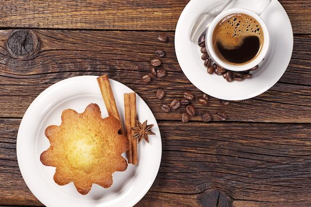 Tazza di caffè caldo e cupcake sulla tavola di legno d'epoca. vista dall'alto
