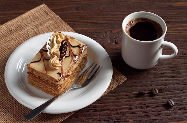 Tazza di caffè caldo e deliziosa torta al miele con crema su un tavolo di legno marrone