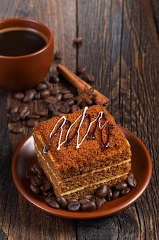 Tazza di caffè caldo e torta di miele sul tavolo di legno scuro
