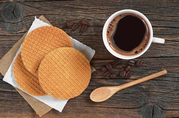 Tazza di caffè caldo e cialde rotonde con caramello sul vecchio tavolo rustico, vista dall'alto