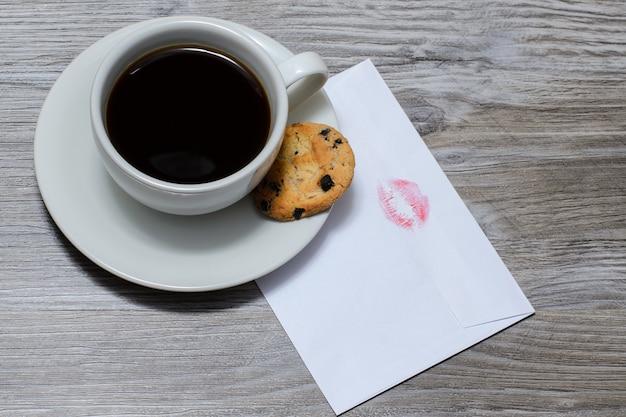 Una tazza di caffè caldo su un piattino con un biscotto al cioccolato, lettera