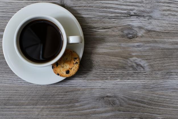 Una tazza di caffè caldo su un piattino con un biscotto al cioccolato