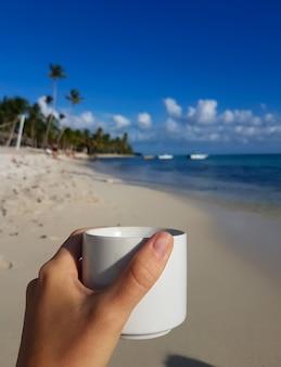 Una tazza di caffè caldo sulla riva di un'isola tropicale.