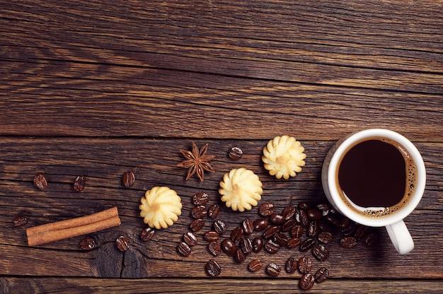 Tazza di caffè caldo e piccoli biscotti sul tavolo di legno scuro, vista dall'alto