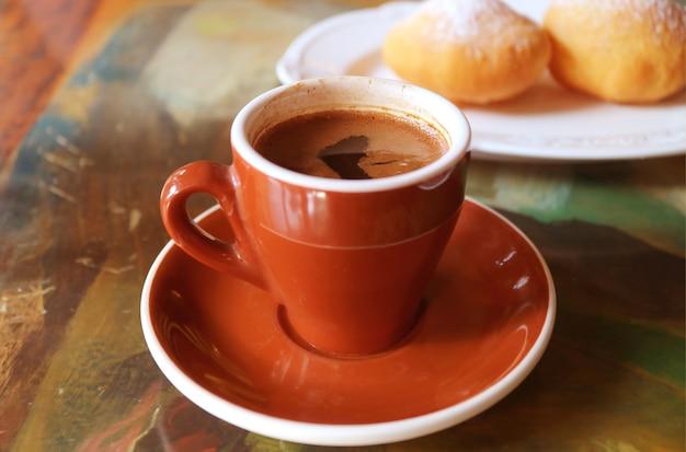 Tazza di caffè caldo con ciambelle georgiane fritte sfocate sullo sfondo Foto Premium