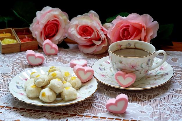 Una tazza di caffè caldo con torta di pasticceria cinese cuori di caramelle rosa e sfondo di rose rosa