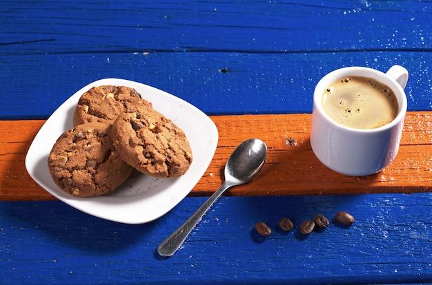 Tazza di caffè caldo con biscotti al cioccolato su un tavolo di legno colorato