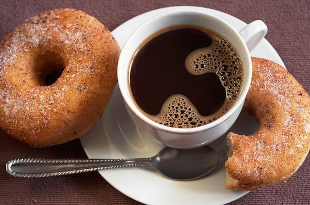 Tazza di caffè caldo con ciambelle classiche sul tavolo da vicino. messa a fuoco selettiva