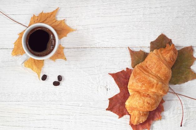 Tazza di caffè caldo con croissant su fondo di legno bianco, vista dall'alto
