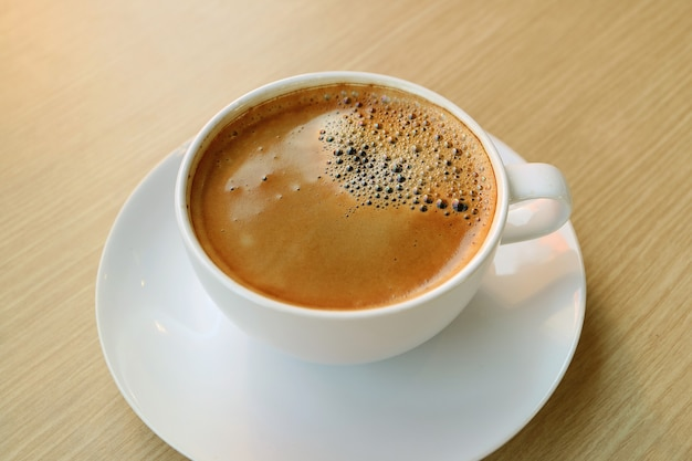 Tazza di caffè caldo con superficie schiumosa isolato su un tavolo di legno