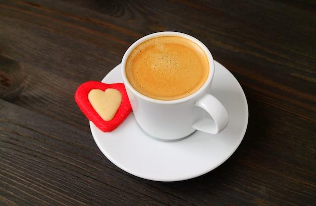 Tazza di caffè caldo con biscotto a forma di cuore sulla tavola di legno marrone scuro