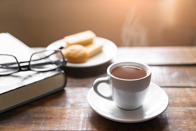 Tazza di caffè caldo con spuntino a vapore e wafer, vecchio libro spesso con i vetri sul vecchio pavimento del tavolo e la luce della finestra della sfuocatura in salone