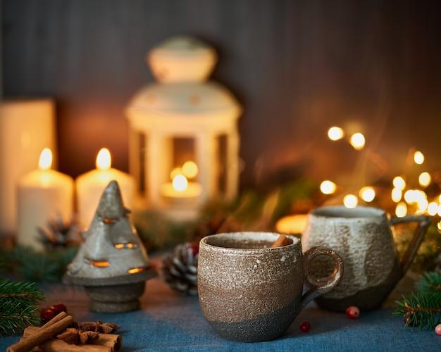 Tazza di bevanda calda su sfondo natalizio. serata accogliente, boccale di vin brulè, decorazioni natalizie, candele e ghirlande luminose.