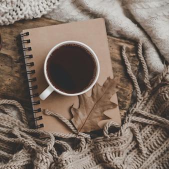 Tazza di bevanda calda su notebookand maglieria