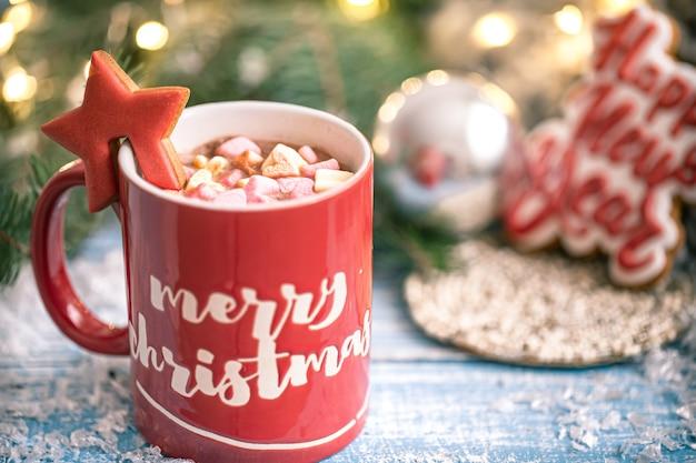 Tazza di bevanda calda con marshmallow e biscotti di panpepato da vicino. concetto del nuovo anno e del comfort domestico invernale.