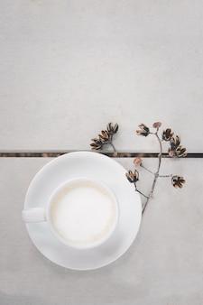 Tazza di latte caldo caffè d'arte sul pavimento di legno sfondo di colore bianco e fiori secchi, in vista dall'alto.