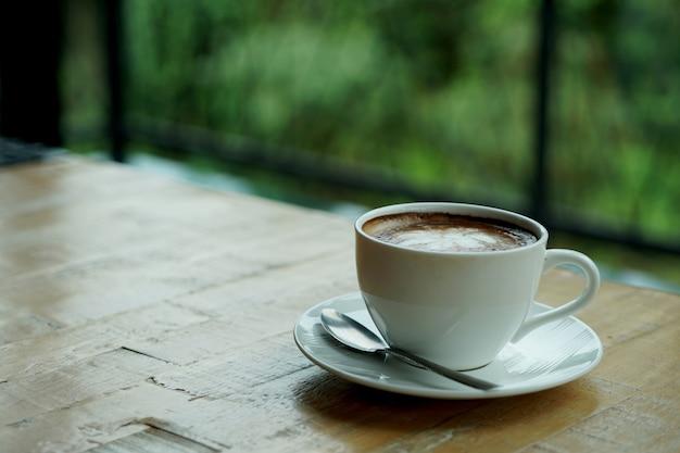 Una tazza di caffè latte art caldo su un tavolo di legno